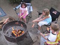 My kids roasting hotdogs around the campfire